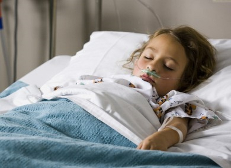 little girl laying in hospital bed