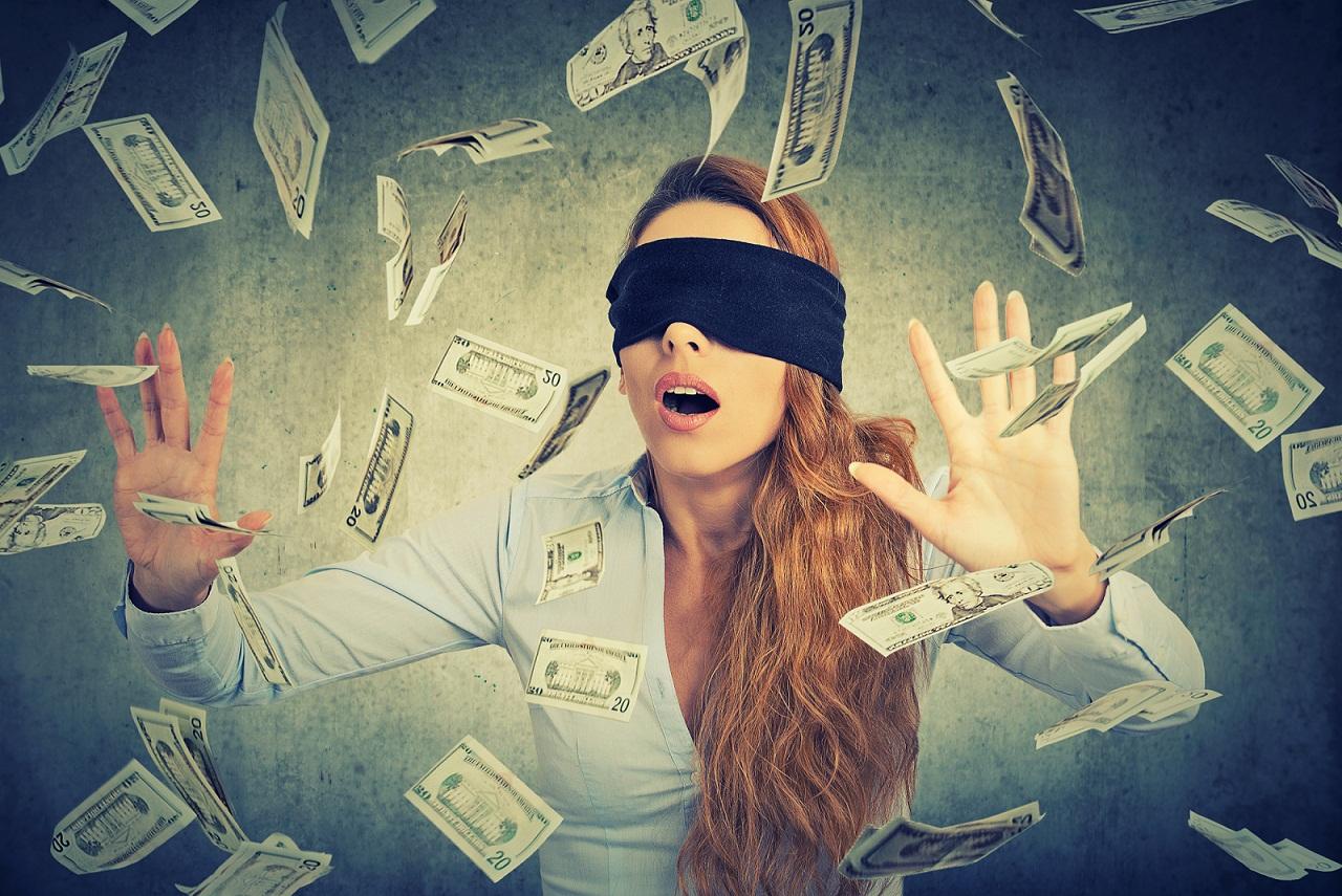 woman blindfolded grasping for money