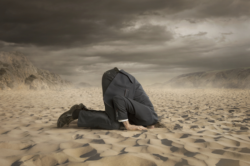 man in suit with head in the sand