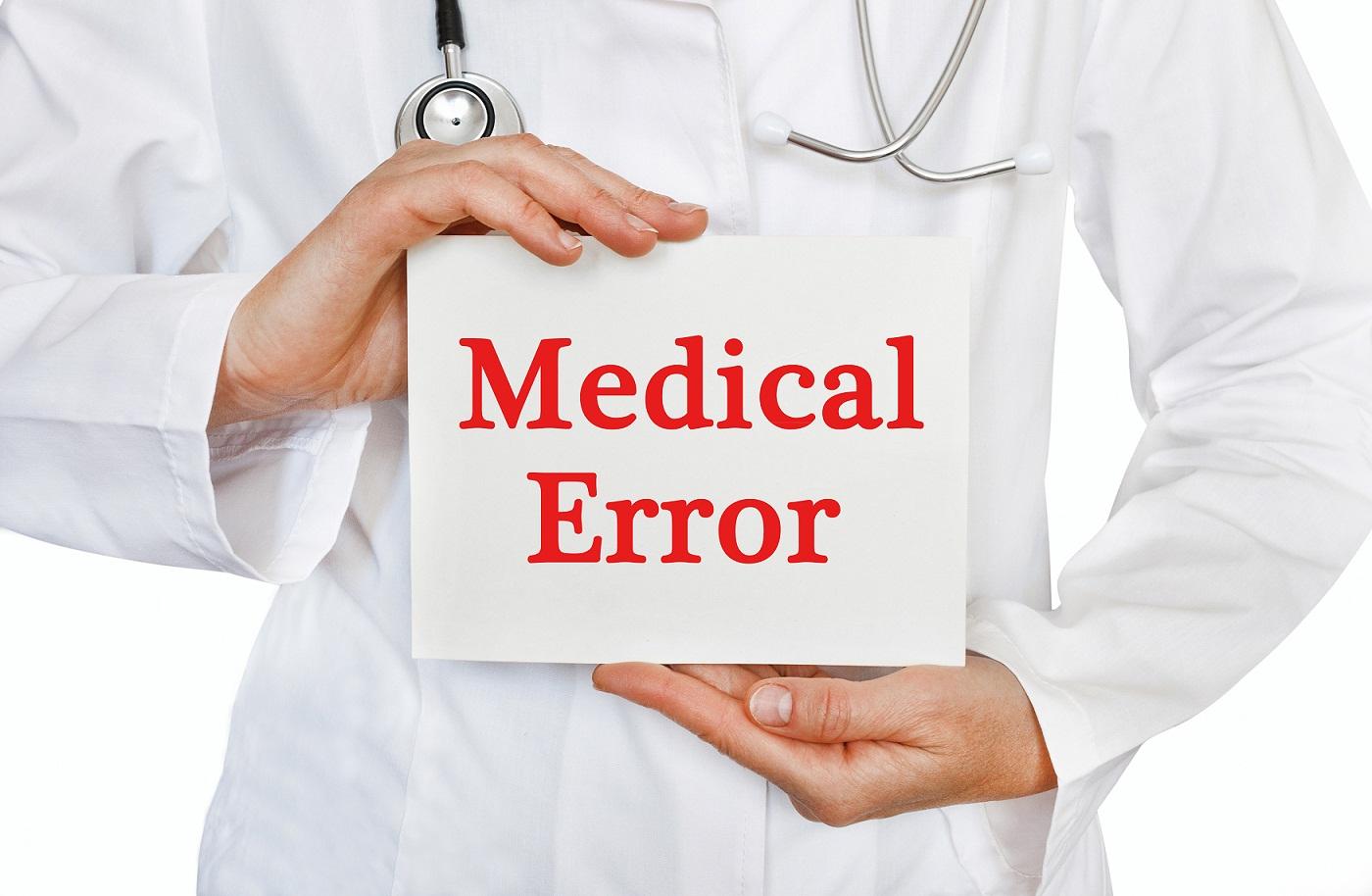 "doctor holding sign saying ""medical error"""