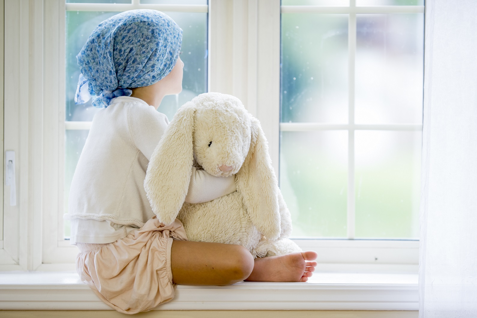 child with cancer looking out window