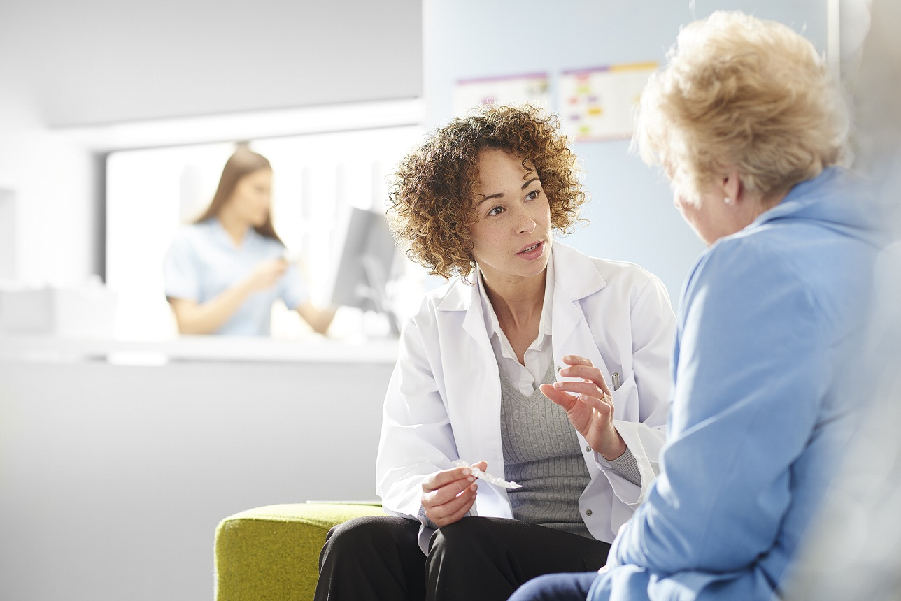 female doctor talking to elderly patient