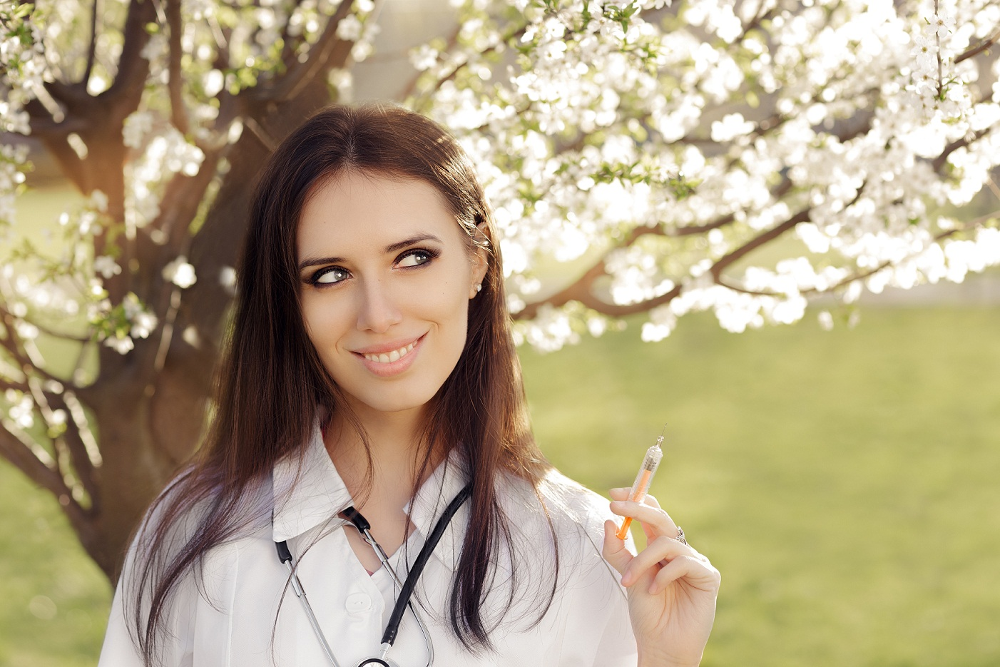 doctor holding a syringe next to a tree