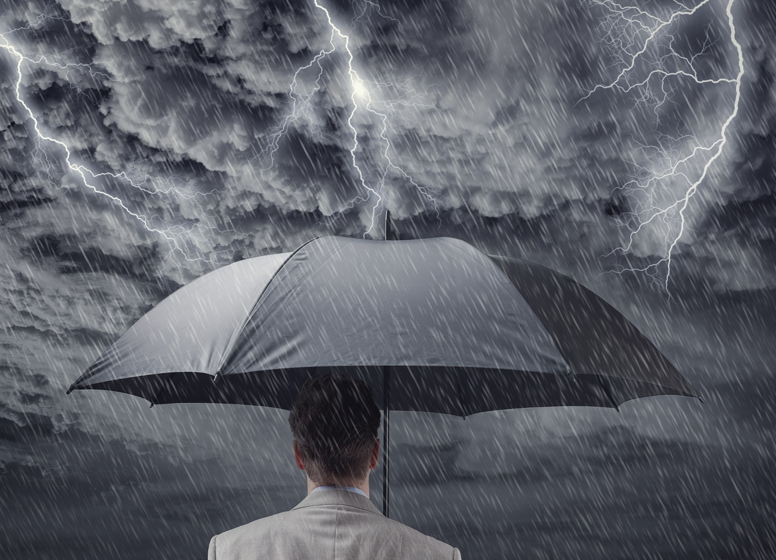 Businessman with umbrella sheltering from approaching storm