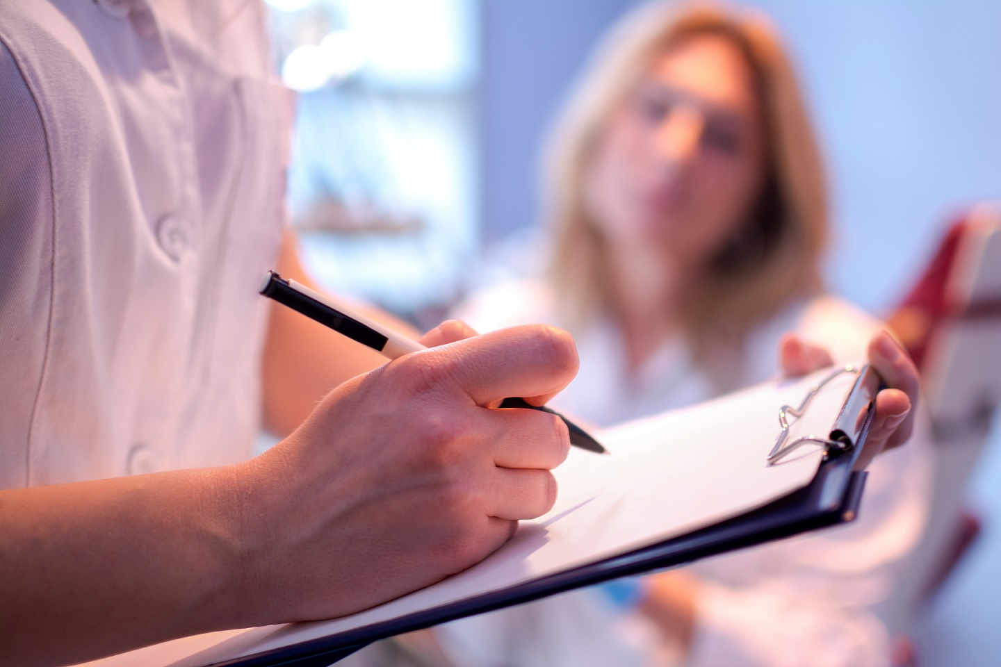 doctor writing on chart as patient looks on