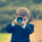 boy in suit looking through telescope