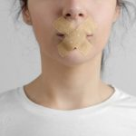 woman's mouth taped shut